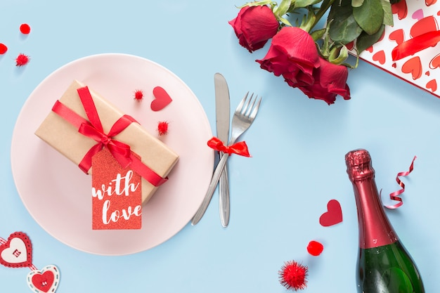 Gift with label on plate near cutlery, roses and bottle of champagne