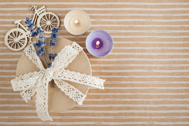 Gift with lace bow, lavender flower and lit candle