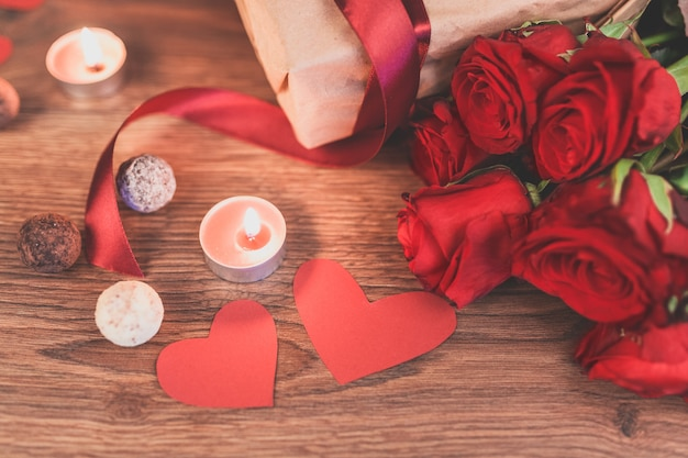 Gift with lighted candles and hearts