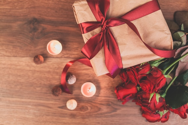 Gift with lighted candles and roses seen from above