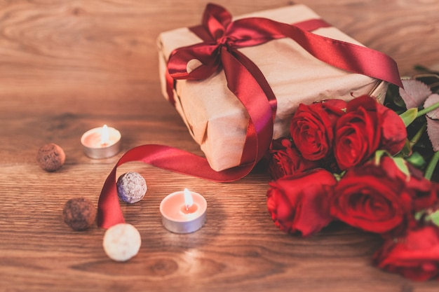 Gift with lighted candles and roses