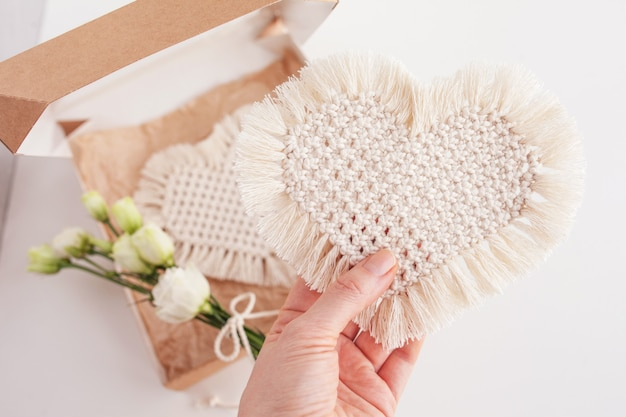 Gift  with macrame decor. heart - symbol of holiday.  natural materials, cotton thread. eco decorations, ornaments, hand made decor in woman hand.