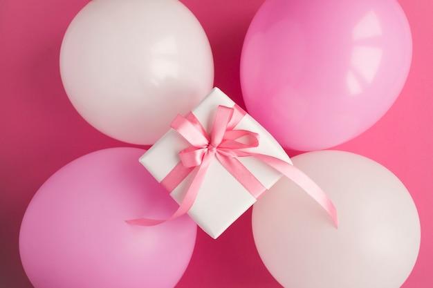 Подарок с розовыми и белыми шарами на розовом столе. вид сверху. крупный план.
