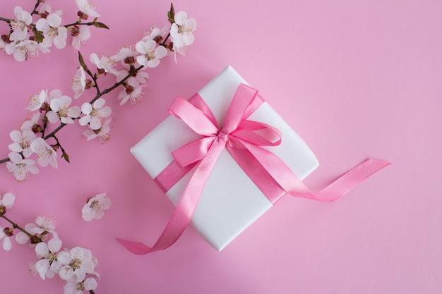 ピンクの弓と開花木の枝のギフト