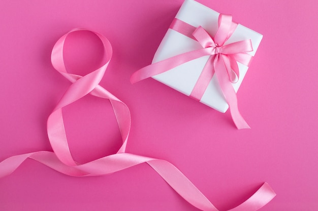 Gift with pink  bow and  pink number eight ribbon. top view. copy space.