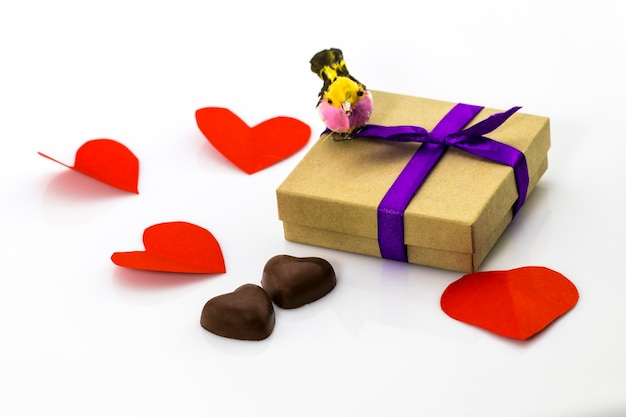 Gift with purple ribbon and candies in shape of heart on white background valentine's day