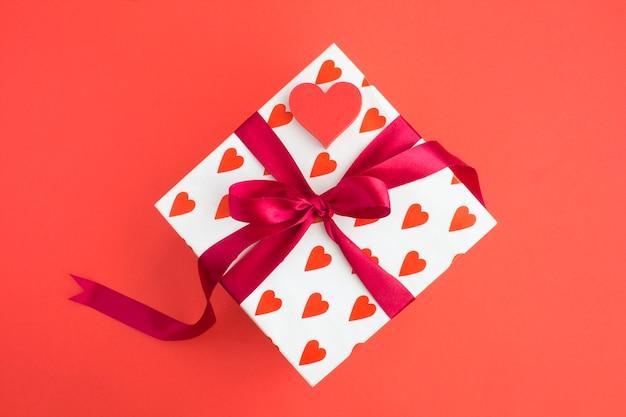 Подарок с красным бантом и красным сердцем в центре красного