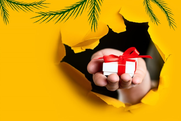 A gift with a red bow in hand emerges from a ragged hole in yellow paper background