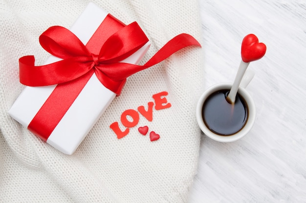 Gift with a red bow on a knitted surface, coffee with a spoon with a heart-shaped decor on a white table
