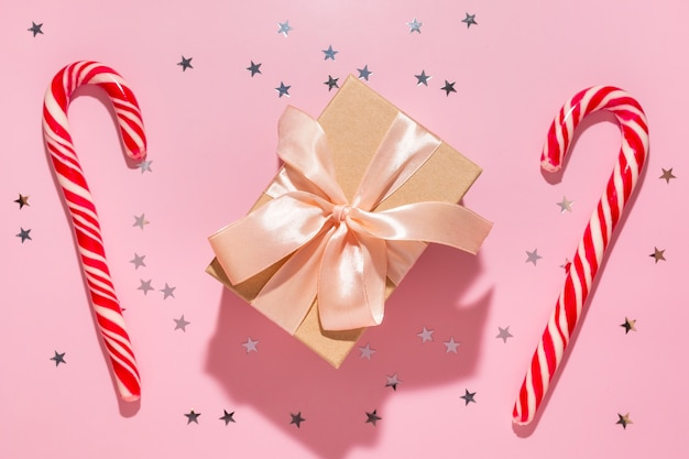 Подарок с красными рождественскими конфетами и звездами конфетти льется на пастельный розовый фон, вид сверху. плоская планировка. праздник нового года, концепция атмосферы праздника