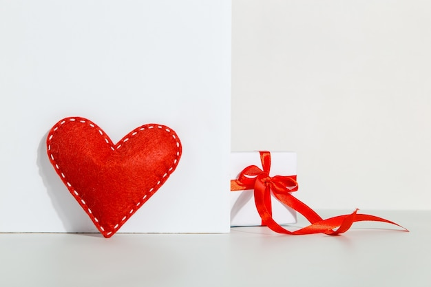 Gift with a red ribbon and heart on a white, the concept of the valentines day
