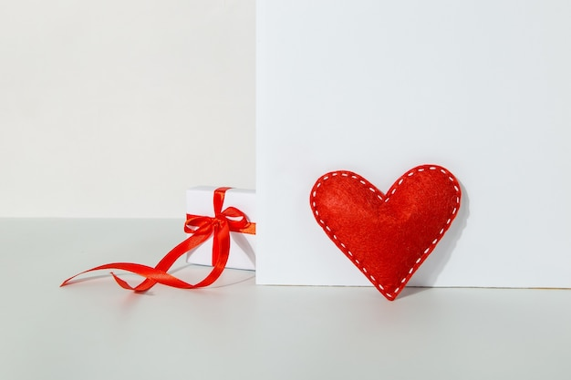 Gift with a red ribbon and heart on a white