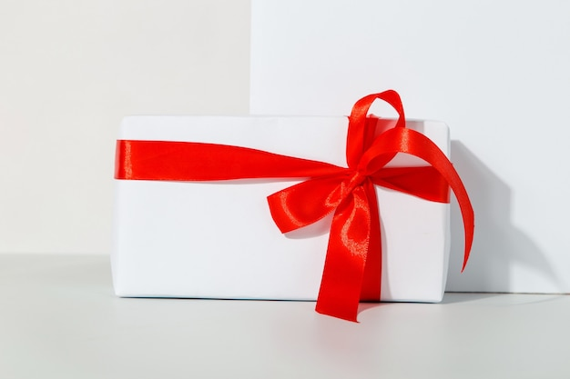 Gift with a red ribbon on a white, the concept of the holiday, congratulations.