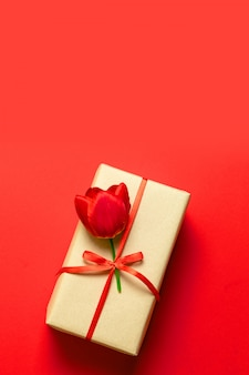 Gift with red satin bow and red flower on red background. flat lay, top view, copy space
