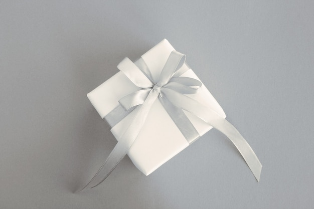 Gift with tied gray bow in the center of the gray  background. top view. copy space.
