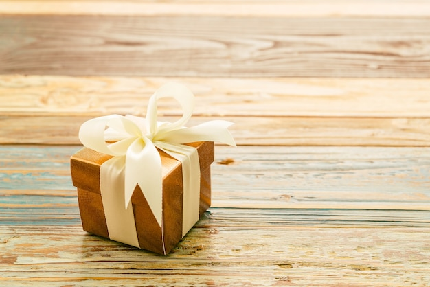 Gift with a white bow on a wooden table