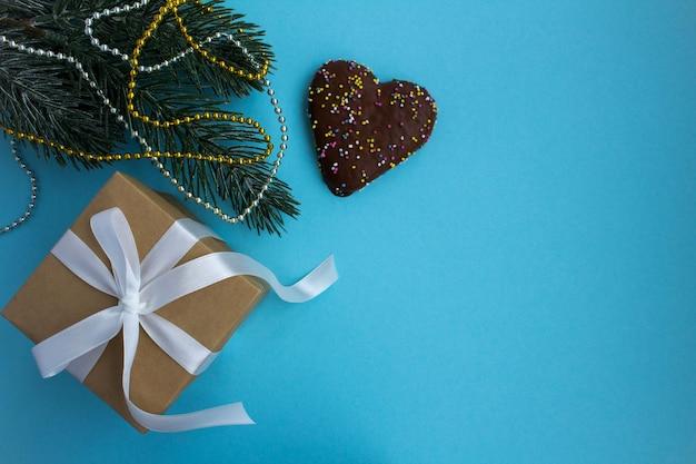 Подарок с белой лентой и рождественской композицией на синем фоне. копирование пространства. вид сверху.