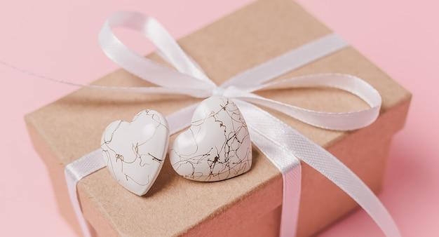 孤立したピンクの背景、愛とバレンタインのコンセプトにwihteハートのギフト