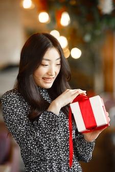 白い箱を保持している赤いギフトの女性。分離された美しい混合白人/アジアモデル。バレンタイン・デー。