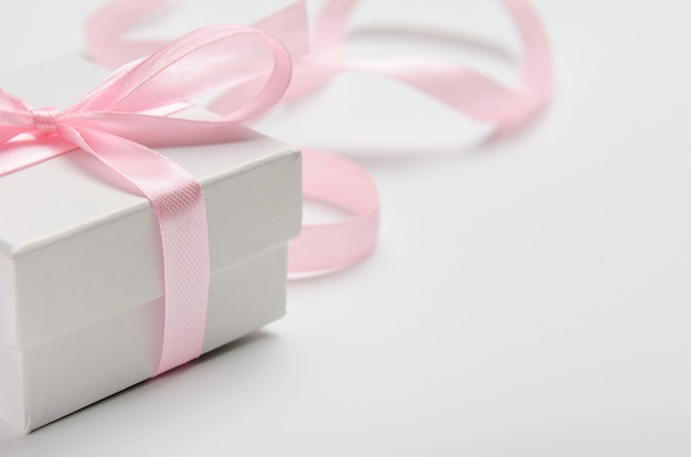 A gift for a woman in white box with a pink ribbon.