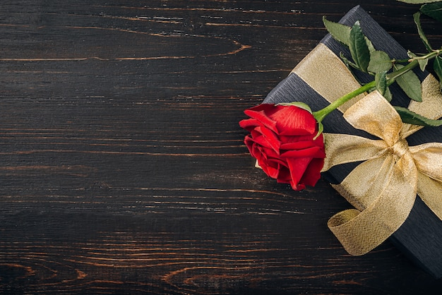 Gift wrapped in black paper and a gold ribbon. on top of the box is a luxurious red rose.