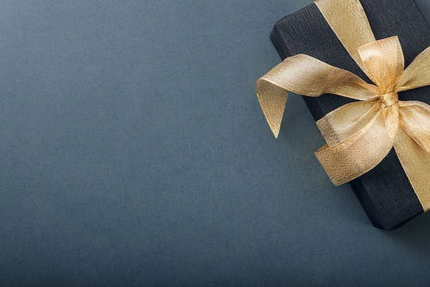 A gift wrapped in black paper and tied with a gold ribbon.