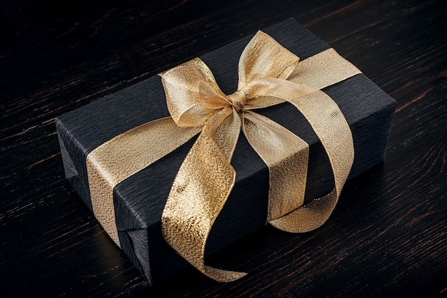 A gift wrapped in black paper and tied with a gold ribbon