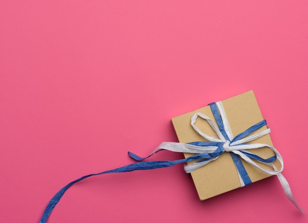 Gift wrapped in brown kraft paper on a pink background, top view
