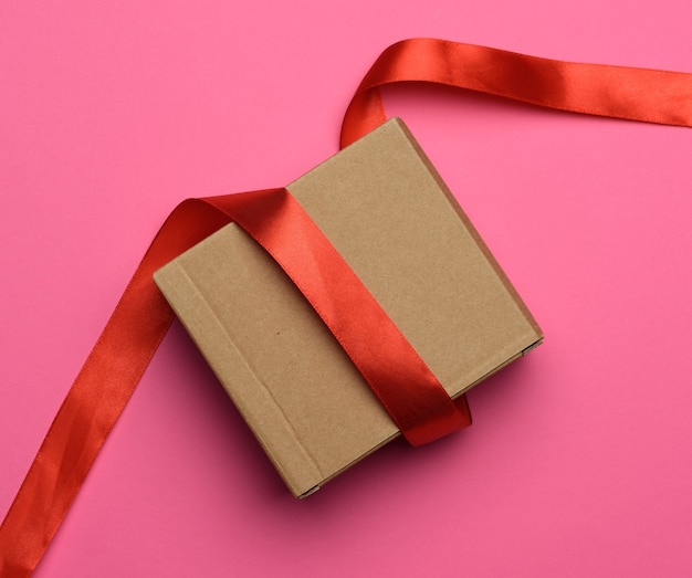 Gift wrapped in brown kraft paper and red ribbon on a pink background, top view