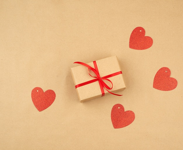 Gift wrapped in brown kraft paper and tied with a thin silk ribbon on a background of paper