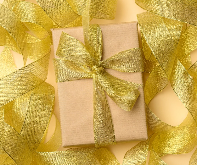 Gift wrapped in brown paper on a twisted golden ribbon, top view