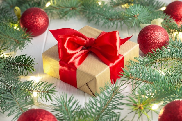 Gift wrapped in craft paper and red ribbon with green branches of christmas tree with led light bulbs, garland and shiny balls