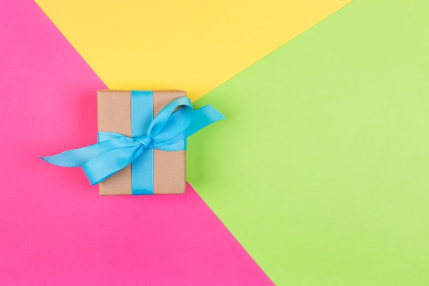 Gift wrapped and decorated with blue bow on colored background with copy space.