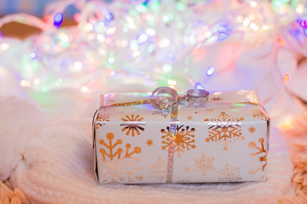 A gift wrapped in a festive packaging tied with a silver ribbon on a knitted white product on a background of bokeh of different-colored lights. christmas preparations concept