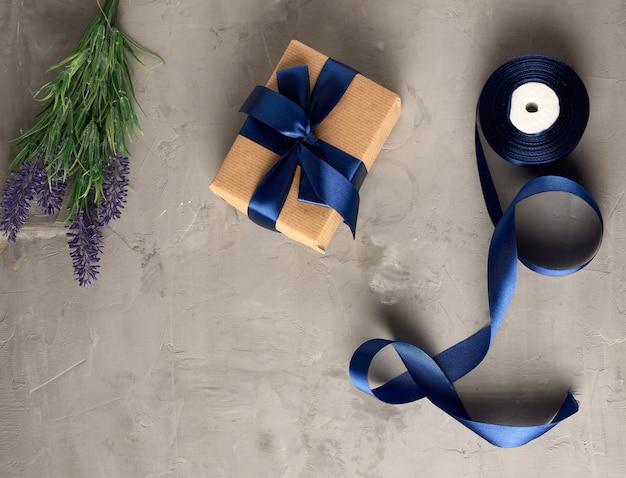 Подарок в коричневой крафт-бумаге и перевязан синим шелковым бантом.