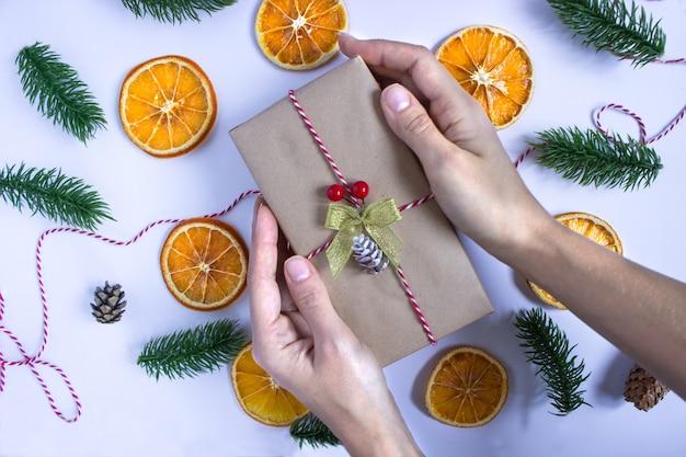 Подарок в крафт-бумаге в руках на белом фоне с сушеными дольками апельсина, еловыми ветками и шишками