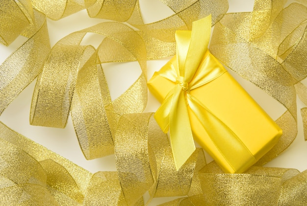 Gift wrapped in paper on a twisted golden ribbon background, festive background, top view
