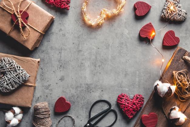 선물 포장 액세서리. 회색 배경에 공예 종이 선물. 발렌타인 데이, 깜짝 및 목화 꽃