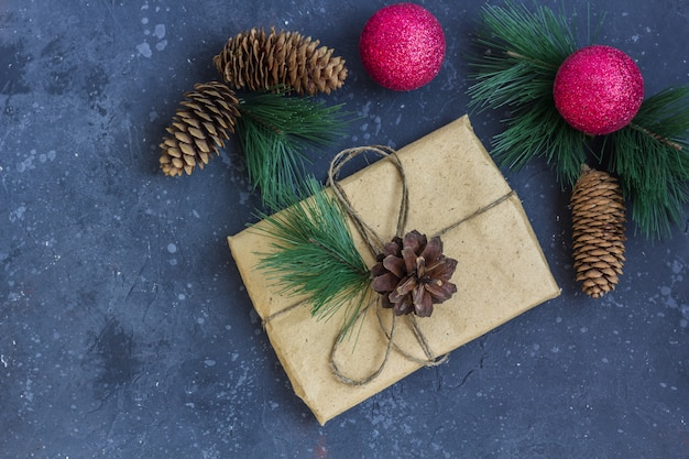 Gift wrapping in kraft paper with christmas decoration on a dark background