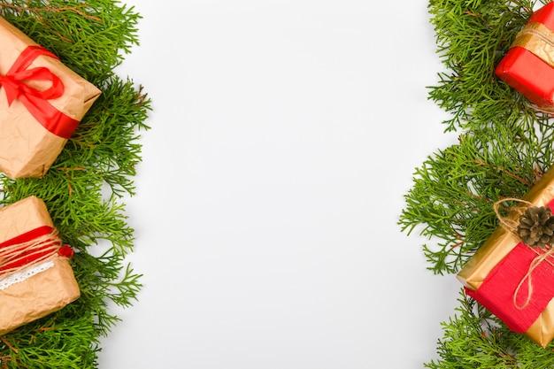 白いスペースに紙で作られたギフト包装。緑の枝。執筆のための場所。上からの眺め。クリスマスツリーの枝と手作りのクラフトラッピングペーパーギフト、白。