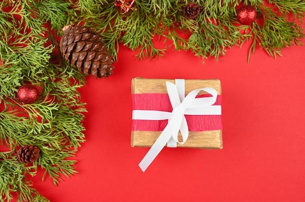 Подарочная упаковка на красном фоне с рождественскими украшениями, вид сверху.
