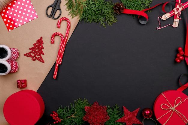 Подарочная упаковка. упаковка современных коробок для рождественских подарков в стильную серую бумагу с атласной красной лентой. стол вид сверху с ветвями ели, украшение подарка.