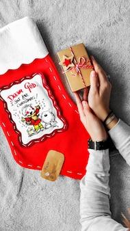 Процесс упаковки подарков. красный рождественский носок подарки в крафтовой бумаге. праздничная атмосфера. новогодний декор. минималистичная подарочная упаковка.
