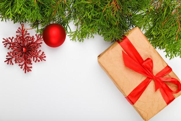 Подарочная упаковка с красным бантом на белом пространстве. хвойные зеленые ветви на белом пространстве. вид сверху. место для письма. рождественское пространство.