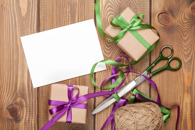 Gift wrapping with greeting card, boxes and scissors over wooden table