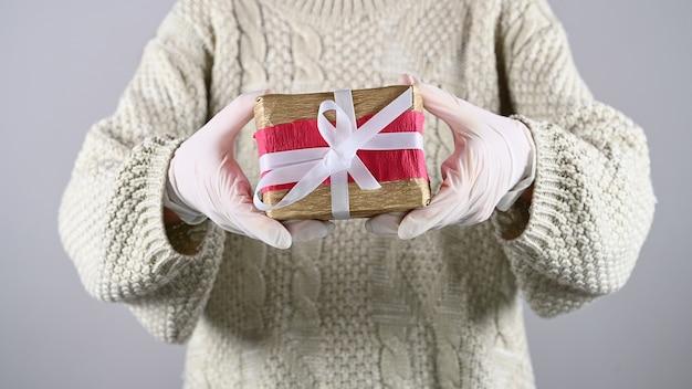 Упаковка подарков в резиновых перчатках. девушка держит подарочную упаковку в резиновых перчатках.