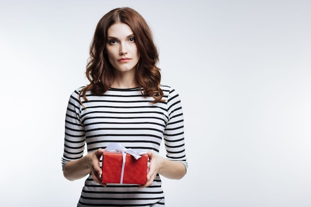 Gift for you. pretty auburn-haired young woman in a striped pullover holding a beautifully wrapped gift box while posing on grey background