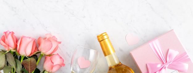 バレンタインデーの休日のギフトデザインコンセプトの大理石の白いテーブルの背景にギフトボックスとピンクのバラの花。