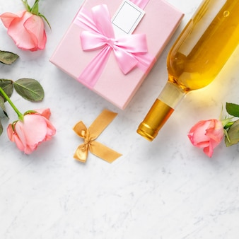 Giftbox and pink rose flower on marble white table background for valentine's day holiday gift design concept.