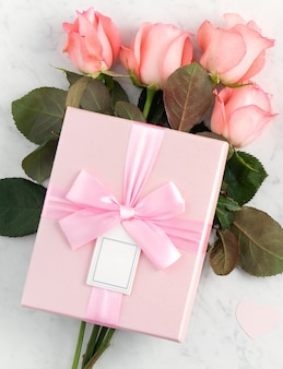 Giftbox and pink rose flower on marble white table surface for mother's day holiday greeting design concept.